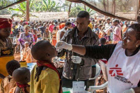 Ärzt*innen ohne Grenzen bei der medizinischen Versorgung eines Kindes. Im Hintergrund eine Menschenmenge