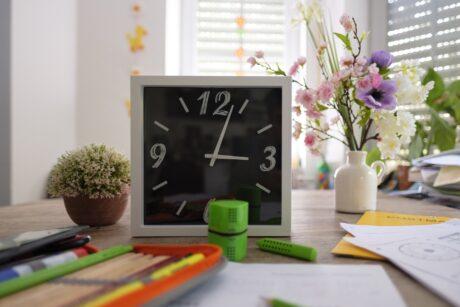 Schreibtisch mit Uhr und Schreibutensilien