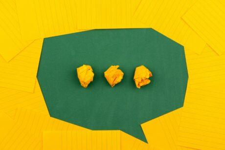 Sprechblase aus grünem Karton, darauf drei Punkte aus zusammengeknülltem gelben Papier