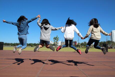 Kinder springen hoch und geben sich die Hände