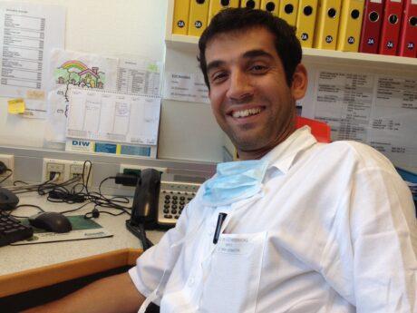 Andishe Attarbaschi, Facharzt f. Kinder- u. Jugendheilkunde, in weißem Mantel am Schreibtisch.