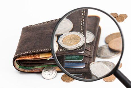 eine Geldbörse mit Münzen, Scheinen und Karten. Eine Lupe schaut genau hin.