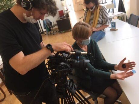 Personen beim Aufnehmen des Videos. Frau hält Hände mit gezeichneten Mikroorganisamen in die Kamera.