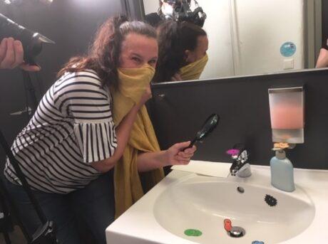 Miranda steht beim Waschbecken und bedeckt Nase und Mund mit einem Schal