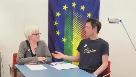 Zwei Menschen diskutieren, im Hintergrund die EU-Flagge, jedoch mit Übergang in bunte Farben.