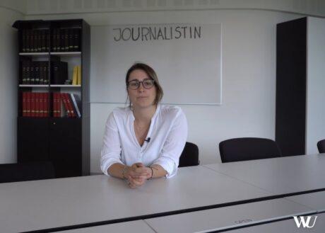 """Eine Frau am Konferenztisch blickt in die Kamera. Dahinter ein Whiteboard mit dem Wort """"Journalistin""""."""