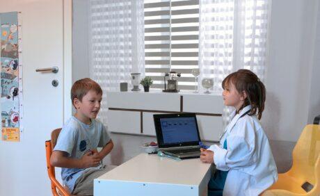 Zwei Kinder sitzem am Schreibtisch und spielen Ärztin und Patient