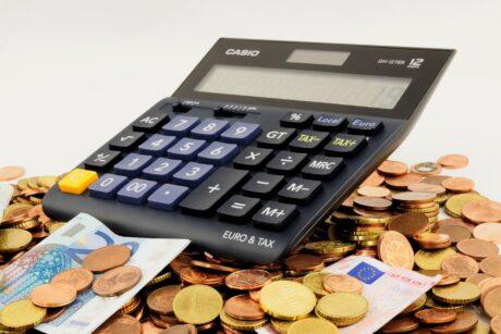 ein Taschenrechner liegt auf einem Haufen Geld