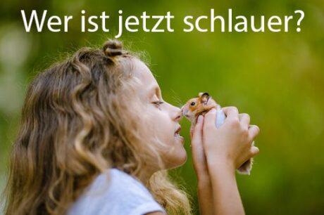 """Mädchen hält Maus in den Händen und gibt ihr einen Nasenstups. Darüber der Text: """"Wer ist jetzt schlauer?"""""""