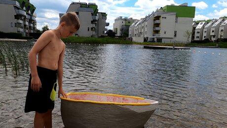 ein Bub am Flussufer mit einem Boot aus Beton
