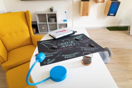 """Auf einem Wohnzimmertisch liegt eine beschriftete Kreidetafel mit """"Start-Up Service"""""""