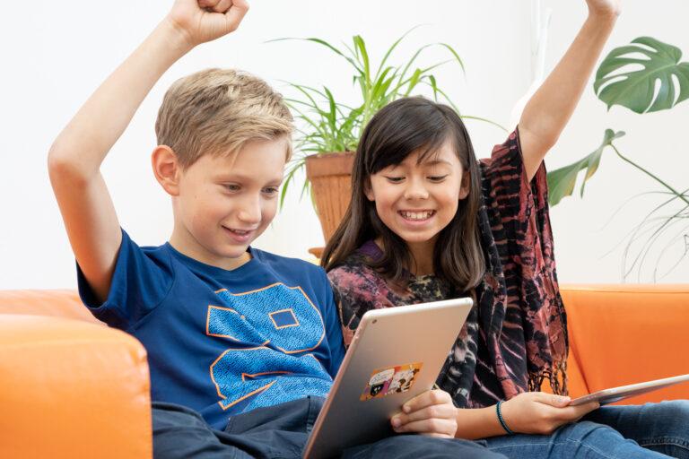 Ein Mädchen und ein Bubsitzen auf einer Couch, blicken auf ihr Tablet und freuen sich.