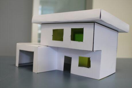Ein Model eines Gebäudes aus Papier. Das Model steht auf einem Tisch.