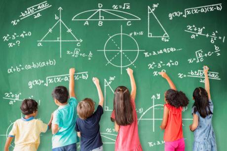 Kinder tun so, als ob sie schwierige mathematische Gleichungen an Tafel schreiben würden