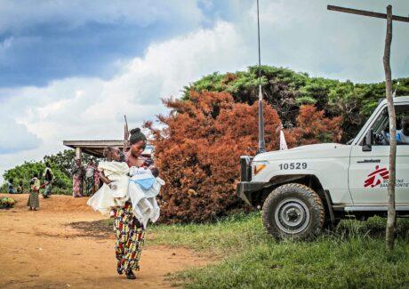 Frau mit mehreren Babys in afrikanimschem Dorf geht zum Auto von Ärzte ohne Grenzen