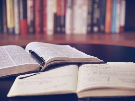 Buch, Kugelschreiber und Notizbuch auf TIsch