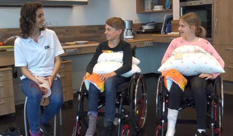 Zwei Kinder versuchen mit Ergotherapeutin die Schwierigkeiten mancher Personen beim Sockenanziehen nachzuvollziehen. Dazu sitzen sie im Rollstuhl und haben einen Polster am Bauch und ein Schwimmflügerl am Knie.