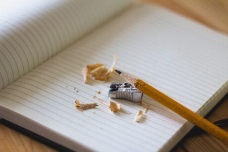 Ein Bleistift liegt neben einem Anspitzer auf einem linierten Papier