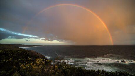Ein Regenbogen am Horizont über einer Meerküste