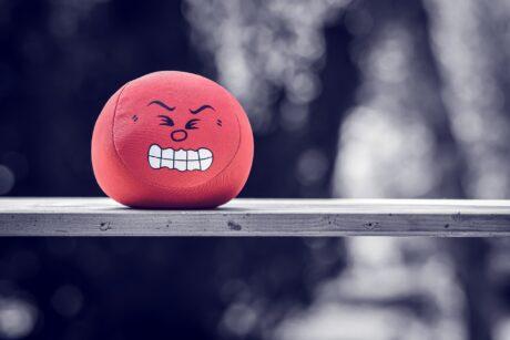 Ein roter Stressball mit aufgedrucktem Smiley, das Anstrengung zeigt