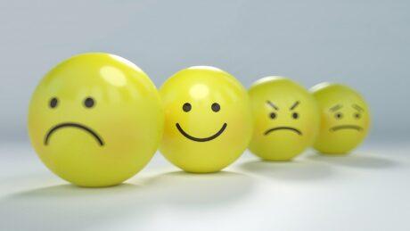 Gelbe Bälle mit aufgedruckten Smilies: traurig, glücklich, zornig, verzweifelt