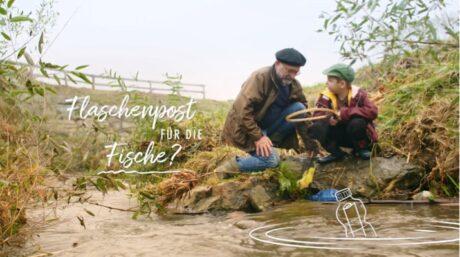 """Ein Mann und ein Kind an einem Bach- oder Flussufer mit der Aufschrift """"Flaschenpost für die Fische?"""""""