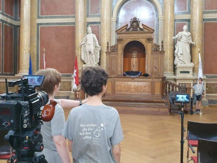 Vier kInder im KinderuniWien T-Shirt nehmen im Festsaal der Universität Wien ein Video auf