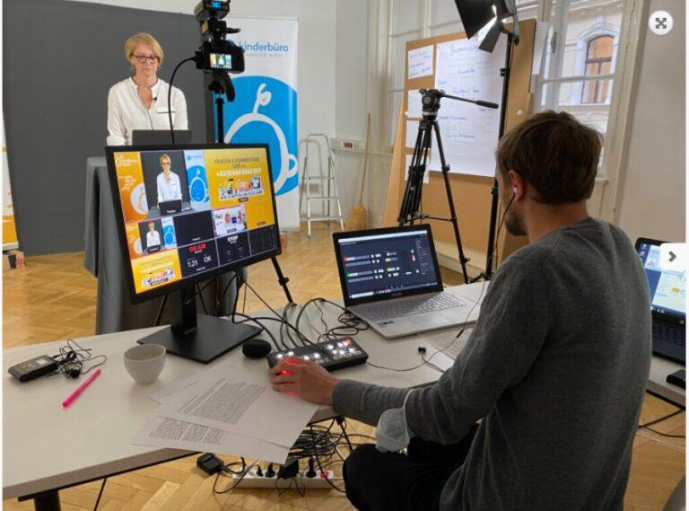 Ein Livestream-Studio mit Kameras, Beleuchtung und zwei Computern. Eine Frau steht vor der Kamera, ein Mann sitzt hinter der Kamera an den Computern.