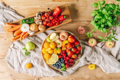 Vogelperspektive: Viele Gemüse- und Obstsorten sowie eine Basilikumpflanze liegen auf Brettern und Schalen auf einem Holztisch.