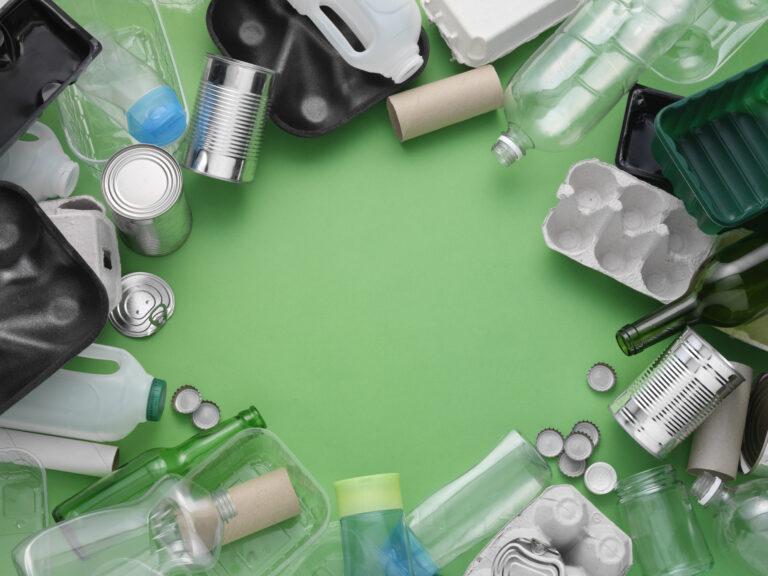 Verschiedene Müllsorten liegen auf einem grünen Tisch, angeordnet in einem Kreis
