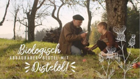 """Ein Mann und ein Kind auf einer Wiese, der Mann liest etwas vor und das Kind hört zu. Das Standbild hat die Aufschrift """"Biologisch abbaubarer Beutel mit Distelöl!"""""""