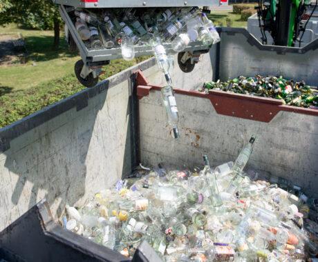 Weißgläser werden von einer ein paar Meter über dem Boden liegenden Maschine aus dem Altglascontainer in einen großen Glasbehälter hinabgeworfen